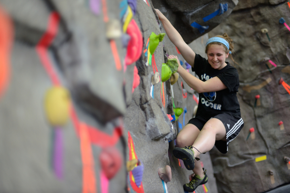 student climbs rock wall at pride recreation center