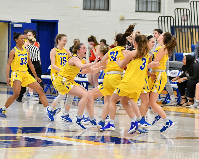 Women's basketball team celebrate on the court