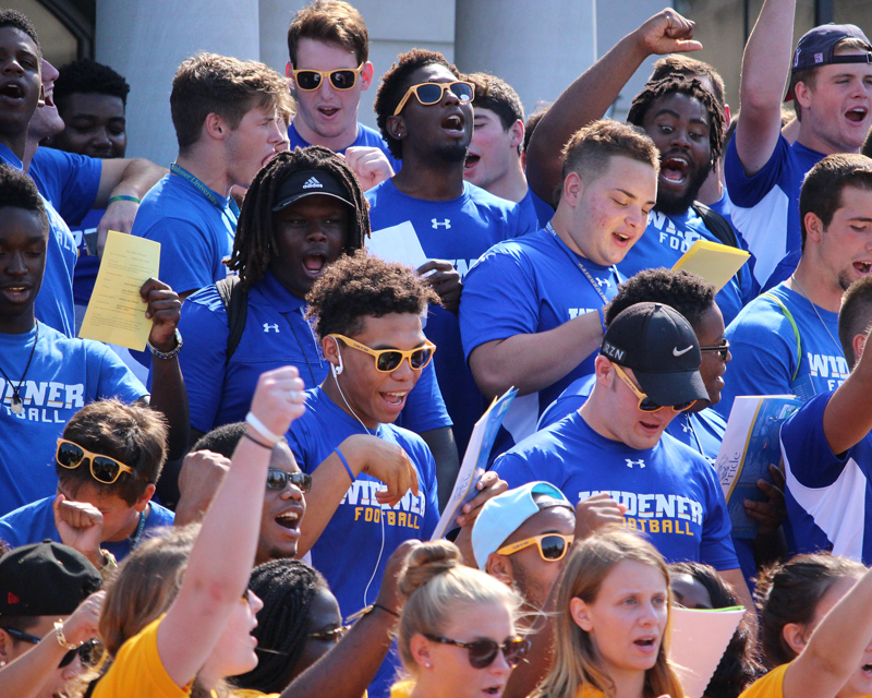 Football players sing the fight song after convocation