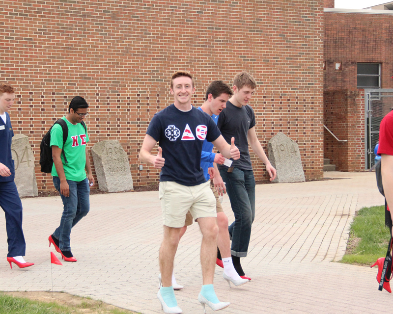 Male students wear high heels to take part in Walk A Mile in Her Shoes event