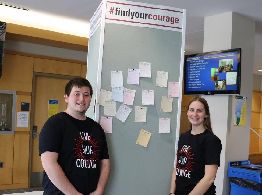 Courage Day student volunteers at bulletin board