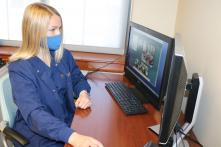 Female nursing student monitors patients remotely on a computer screen.