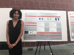 Autumn Campbell poses in front of a research poster presentation.