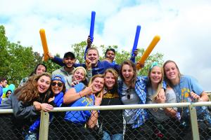 group of student cheering at homecoming football game