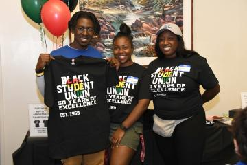 Black Student Union 50th anniversary celebration with 3 students wearing or holding commemorative T-shirts