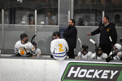 Ice hockey team on the bench with coaches