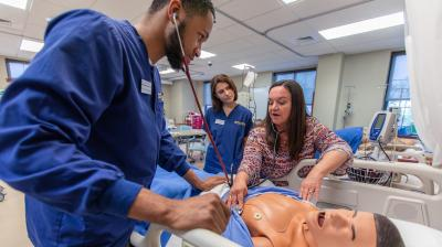 nursing students work with faculty member in simulation lab