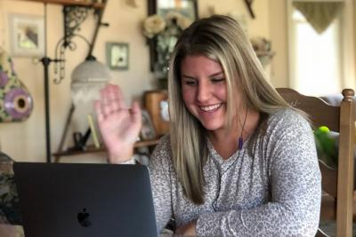 Samantha Begley waves to her computer as she meets with a group of incoming business students.