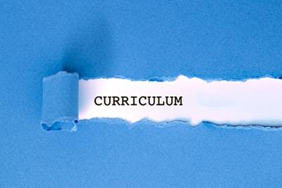 Blue sheet with a tear pulled back to reveal the word 'curriculum'