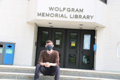 Student in mask sits in front of Wolfgram Memorial Library