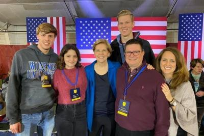 Widener students and faculty pose with Democratic primary candidate Elizabeth Warren in front of flags in New Hampshire