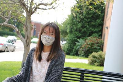 Student wearing mask sits on campus