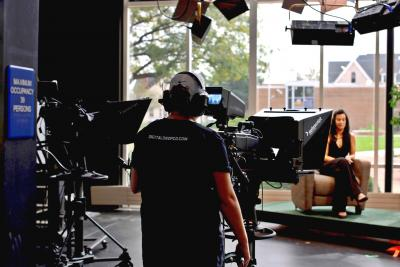 Person filming one of the hosts of the virtual Veterans Parade show in the TV studio