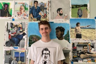 Kevin stands in front of his art