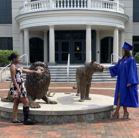 Sisters Arianna and Arielle McRae touch the noses of the Pride statues