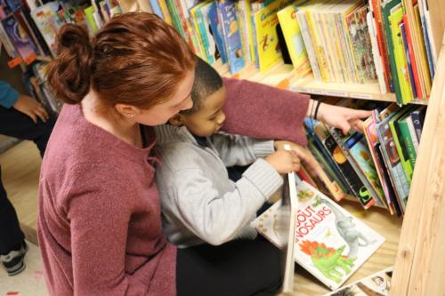 Student helps child pick a book from the Stetser Library