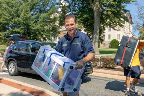 Dean of Students John Downey helps carry student belongings on move-in day.