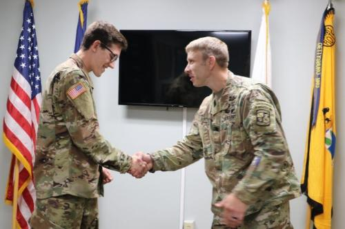 The leader of ROTC shaking a cadet's hand.