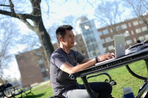 Student studying on laptop, sitting outside at a picnic table