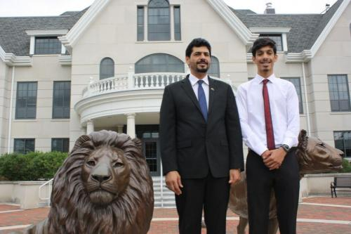 Father and son from Saudi Arabia with lion statue