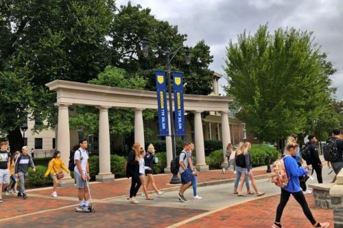 Students walk on campus past We're All Widener banners