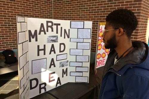 Student looks at MLK Day poster