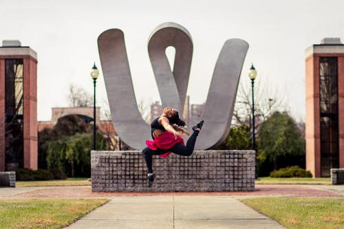Dance student in a mid-air jump in front of the 'W' statue