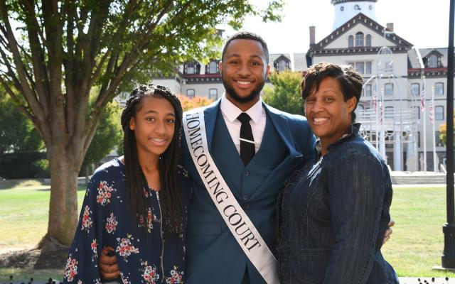 family celebrates student in homecoming court in front of Old Main building
