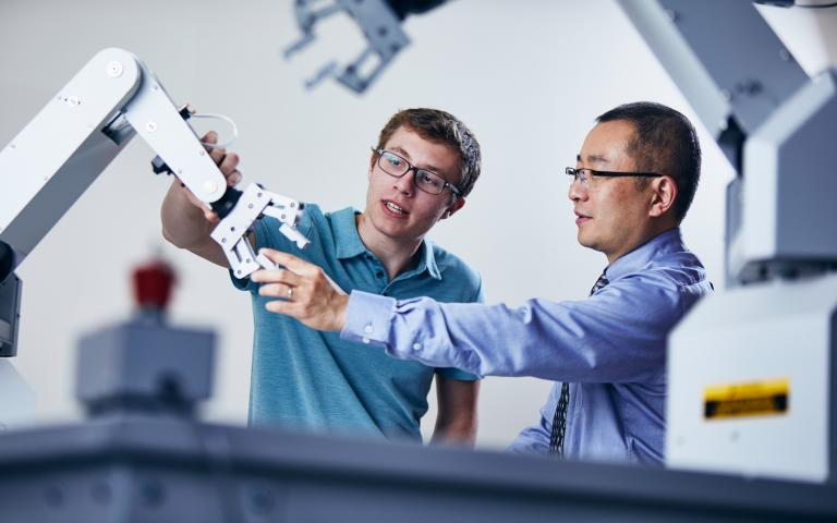 Student and Professor with Robotic Arm