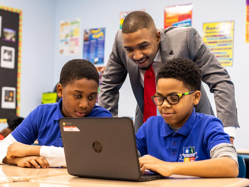 Michael Dixon working with students at a laptop