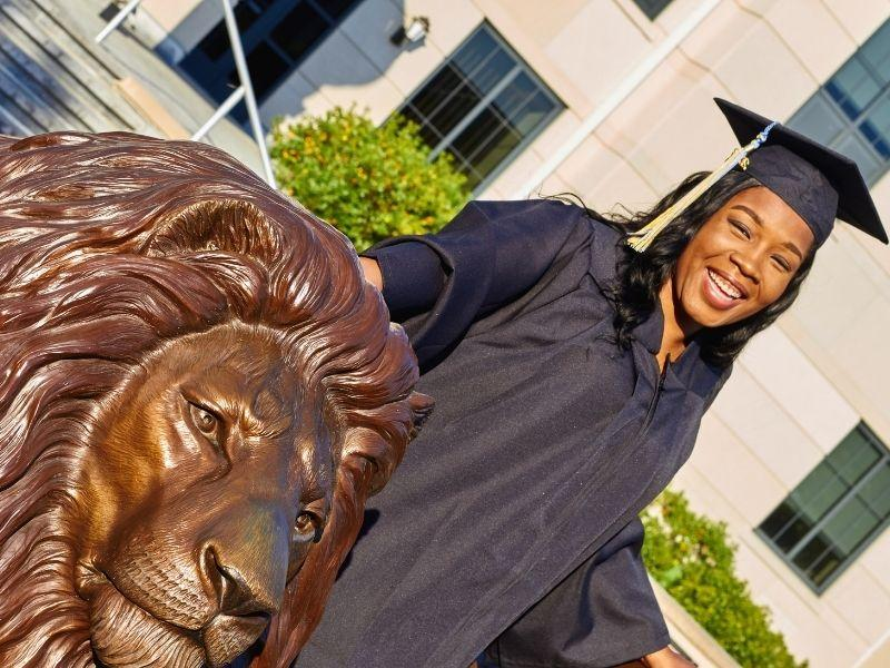 A graduate poses at the Pride statue in her cap and gown.