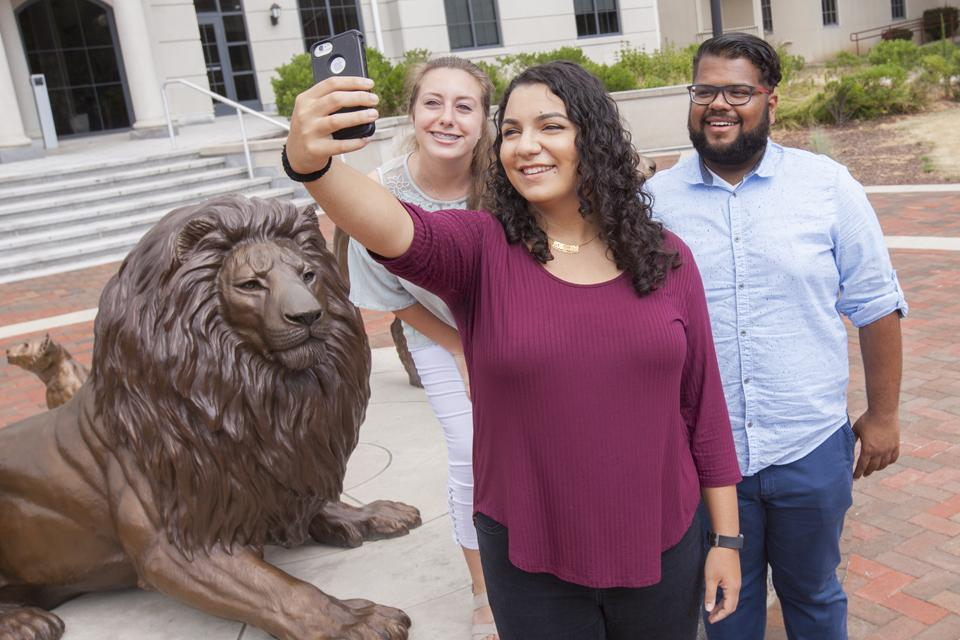 students at lion statue taking selfie