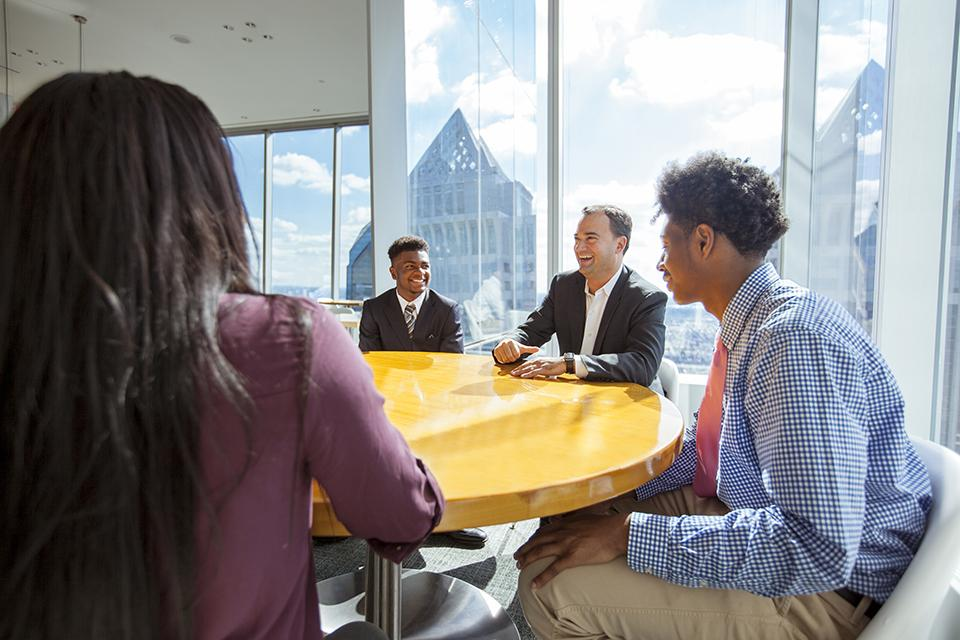Student and alum sitting around a table at Comcast building